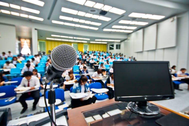 Un écran et un micro disposés sur un bureau devant une classe